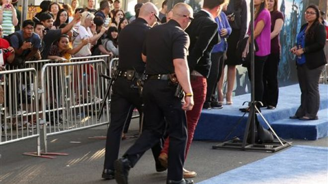 Brad Pitt Attacker is escorted off the red carpet in handcuff by Policemen