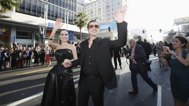 Cast member Angelina Jolie and actor Brad Pitt wave at fans as they arrive at the premiere of